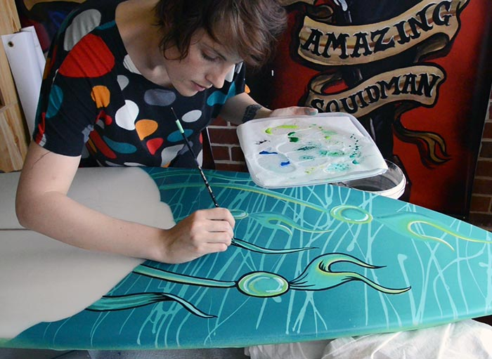 Fieldey hand-painting a surfboard artwork